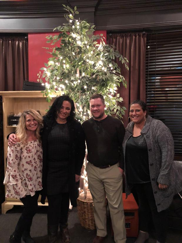 Four people standing in front of a christmas tree