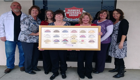A group of women and a man stand outside of a Farmers Insurance office holding a plaque.