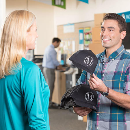 Customer showing The UPS Store franchisee a hat he produces