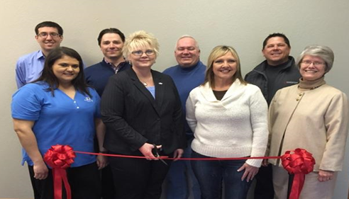 A group of adults cutting a ribbon.