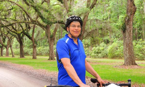 Agent on bicycle in front of trees