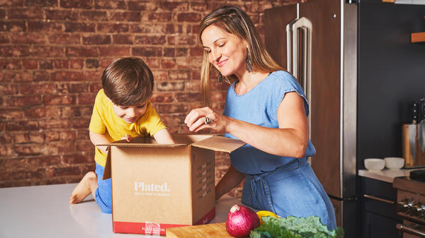 Mother and son in a kitchen unboxing a Plated box