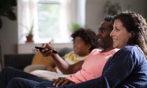 Familia viendo televisión juntos en un sillón