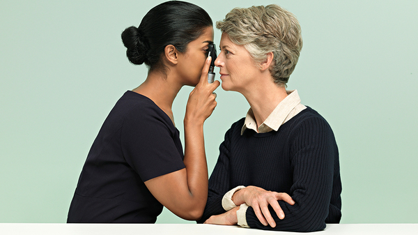 A Specsavers' eye doctor using an instrument to inspect a patients eye.