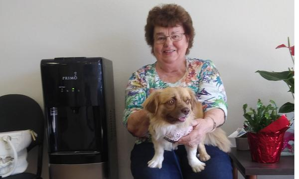 A woman holding a small dog, sitting next to a water cooler in an office