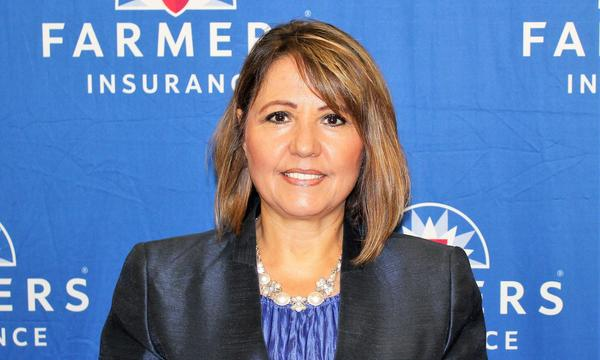 Agent Mary Aranda in front of a blue wall with the Farmers Insurance logo on it