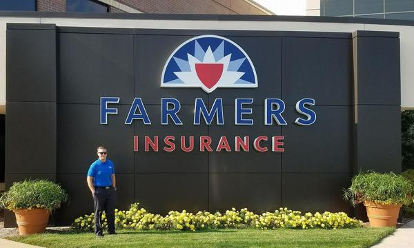 A man standing in front of a Farmers logo