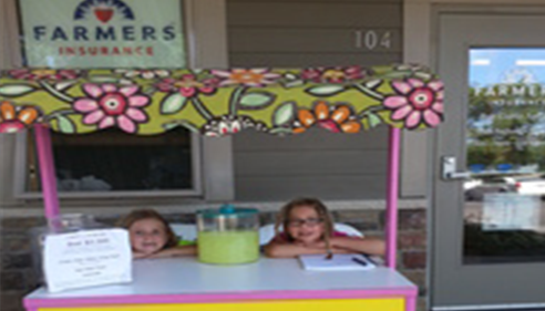 Two girls are sitting at a lemonade stand in the summer