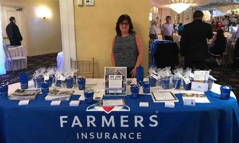 Agent standing behind a Farmers booth at a conference