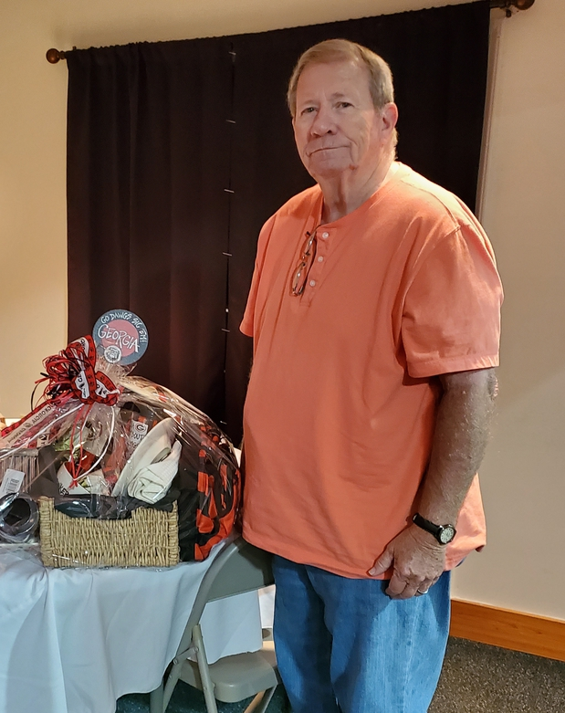Man standing next to a gift basket he won