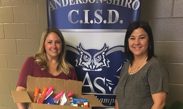 Farmers agent Mynde gives Teacher Nancy Kindle school supplies in front of a blue banner with an owl on it.