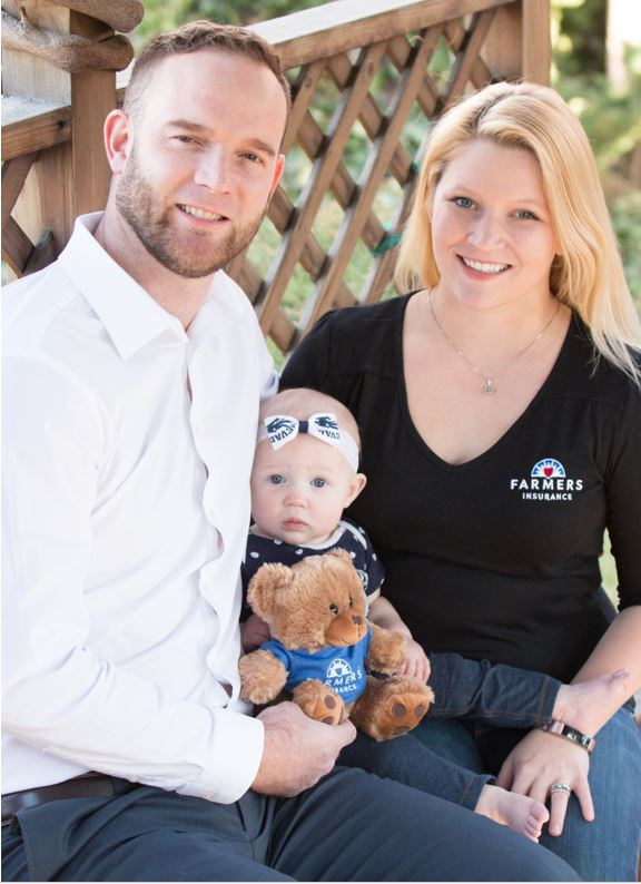 A family photo of the Watty family outside with a teddy bear.