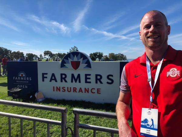 Agent standing by farmers insurance sign