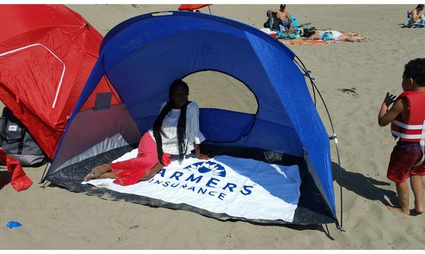 Agent Felicia Traylor with her family at the beach, sitting inside of a Farmers Insurance branded tent.