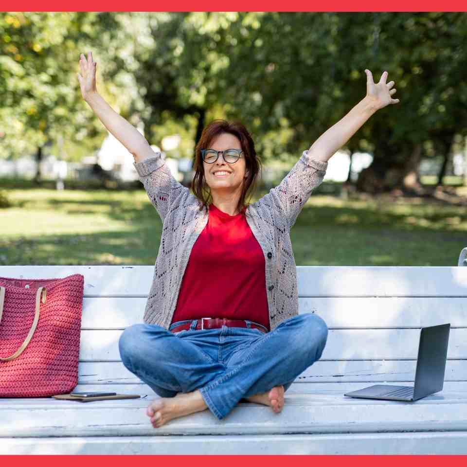 A woman on a park bench throws her hands in the air