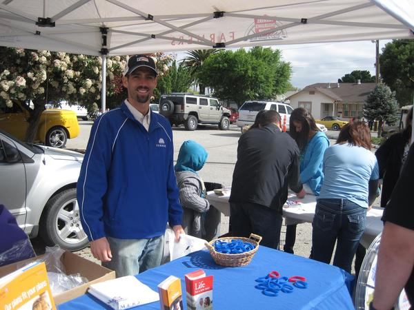 Agent Robert Cullen in front of Farmers Insurance booth at an event