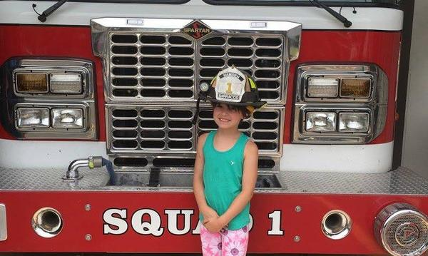 My daughter Max visiting a local fire station with a donation.