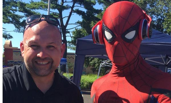 A man smiling at a camera standing next to Spider Man.