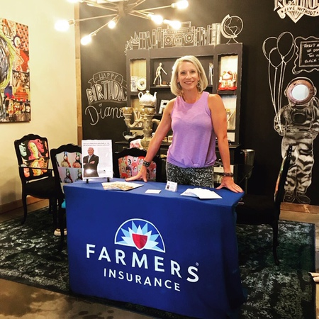 Woman standing behind a table that has the Farmers logo on it