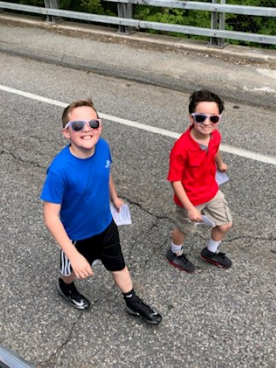 Two young boys walking down the street.