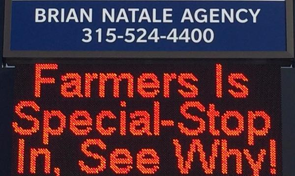 "Electric sign that reads ""Farmers is special - stop in, see why!"""