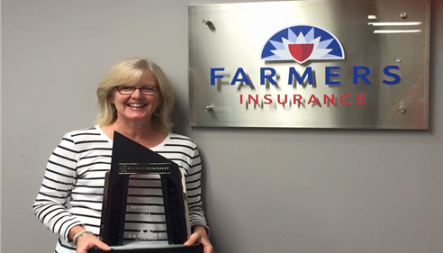 Employee Kerrie Boylan standing in front of the Farmers logo, holding a sales award.