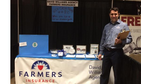 Agent stands with a clipboard in front of a Farmers table at a conference