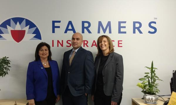 Agent standing with a woman and a man in front of the Farmers logo