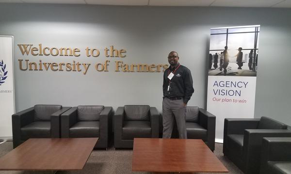 Agent standing next to Welcome to the University of Farmers sign