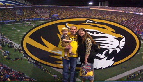 Agent Matt Smith, with his wife Nancy, and their son at the 2014 SEC Championship. They are standing in front of a logo of one of the teams.