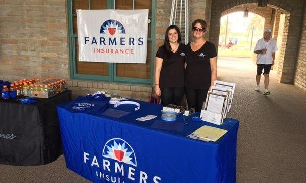 Agent standing with woman behind a Farmers booth