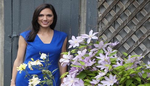 The agent poses in a blue short-sleeved dress next to some flowers
