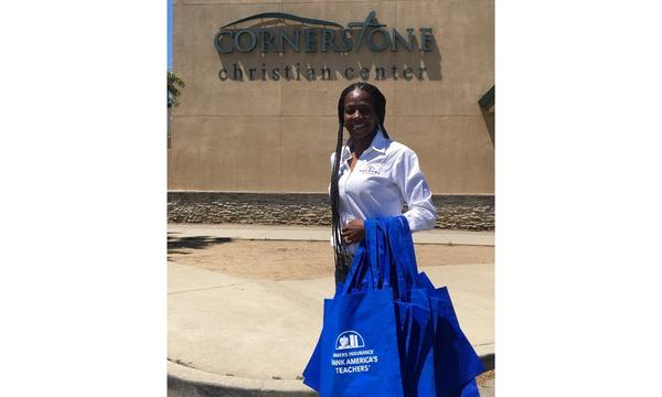 Agent Felicia Traylor holding Thank America's Teachers bags in front of the Cornerstone Christian Center.