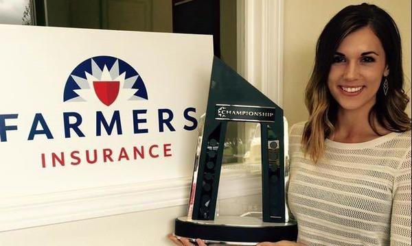 Agent holding her championship award and standing next to a sign with the Farmers logo
