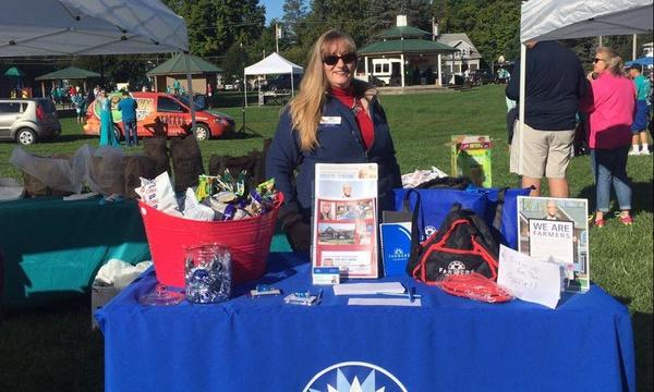 Agent Joyce Felder behind a Farmers Insurance branded information table, at an outdoor event.