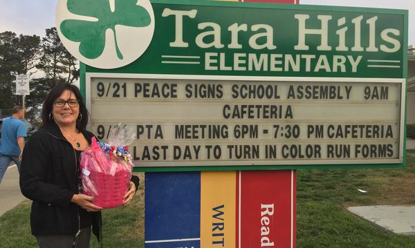 Jessie stands in front of the sign for Tara Hills Elementary