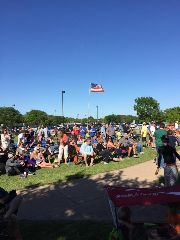 Photo of a large group of people on green grass enjoying themselves at a community BBQ. An american flag blows in the wind.