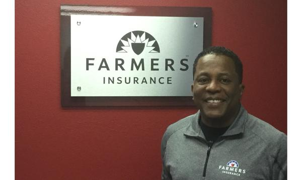Agent Ronald Williams standing next to a plaque with the Farmers logo