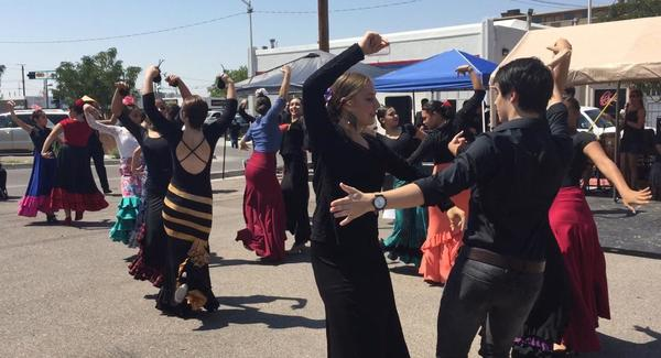A large group of people dance flamenco outside in the sunshine