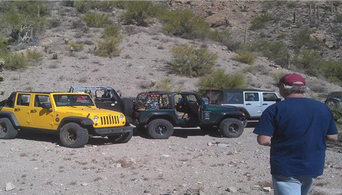 Agent Jacob La Grander standing in front of four jeeps, at the bottom of a mountain.
