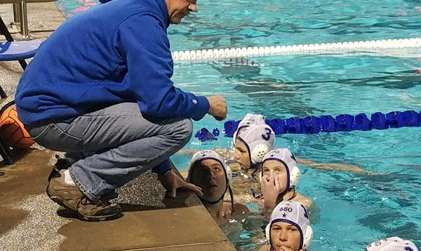 Coach surrounded by young boys water polo team in pool