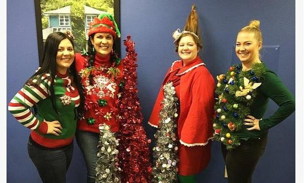 Agent and three women wearing christmas sweaters