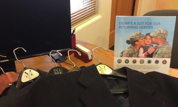 "Three suits laid on on a table, next to a sign that reads, ""Donate a suit for our returning heroes"""