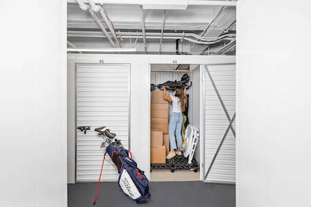 Woman packs her storage unit with baby stroller, golf clubs, boxes and more