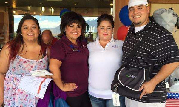 Agent Antoinette Baca standing with two women and a man inside of a golf course clubhouse