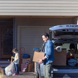 Dad and son carry boxes into their new home.