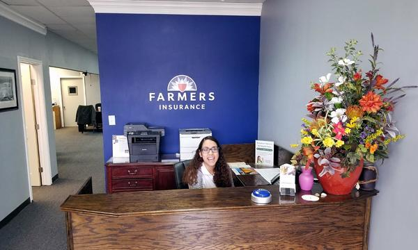 The front desk at Arnold Alaniz Agency, with a woman sitting behind the desk smiling.