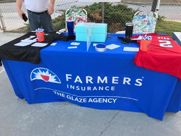 Close up of a blue Farmers Insurance table for The Glaze Agency