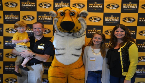 Agent Matt Smith's family posing with a large Tiger mascot.