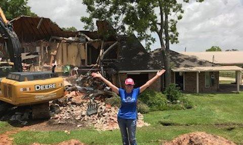 A photo of the agent in front of a demolition site.